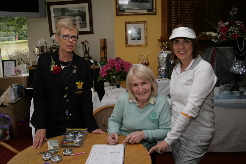 On the desk Carnel Flynn with Lady Captain and Fiona Flanagan